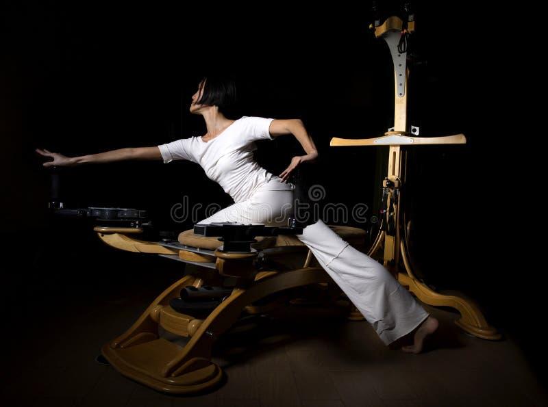 Den Pilates världsförbättraregenomköraren övar kvinnan fotografering för bildbyråer