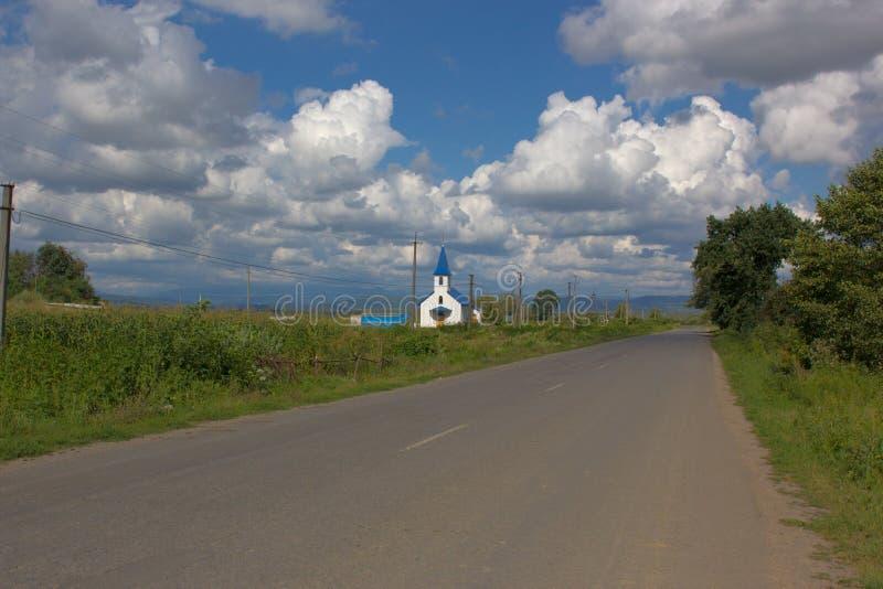 Den pittoreska härliga contrysidevägen med vit och blått kyrktar på det vänstert arkivfoton