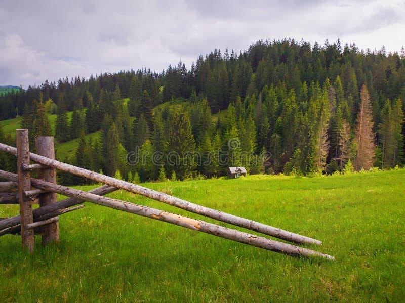 Den pittoreska vårbergplatsen med träsplittringstångstaketet över ett grönt och frodigt betar med ett gammalt hus på dalen arkivfoton