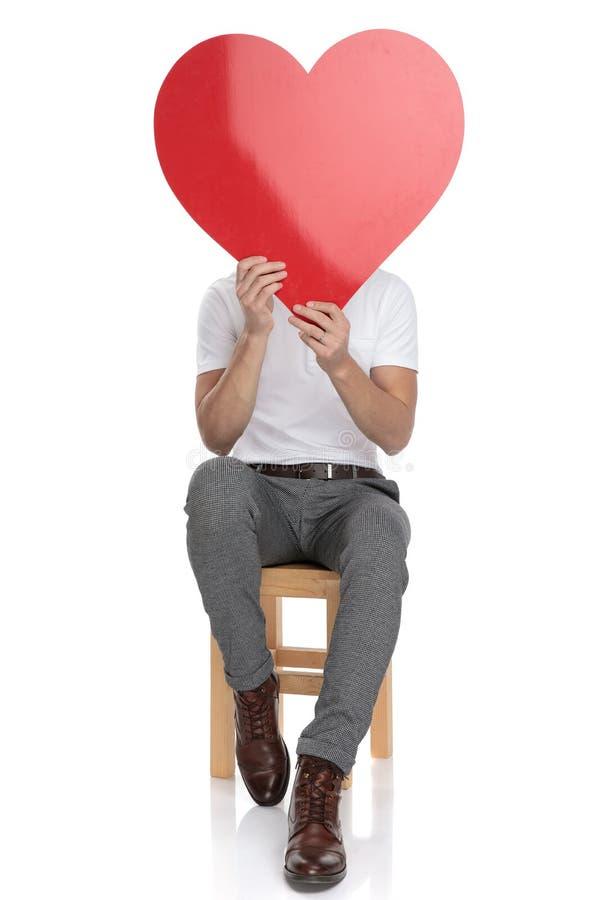 Den placerade mannen täcker hans framsida med en stor röd hjärta arkivfoto