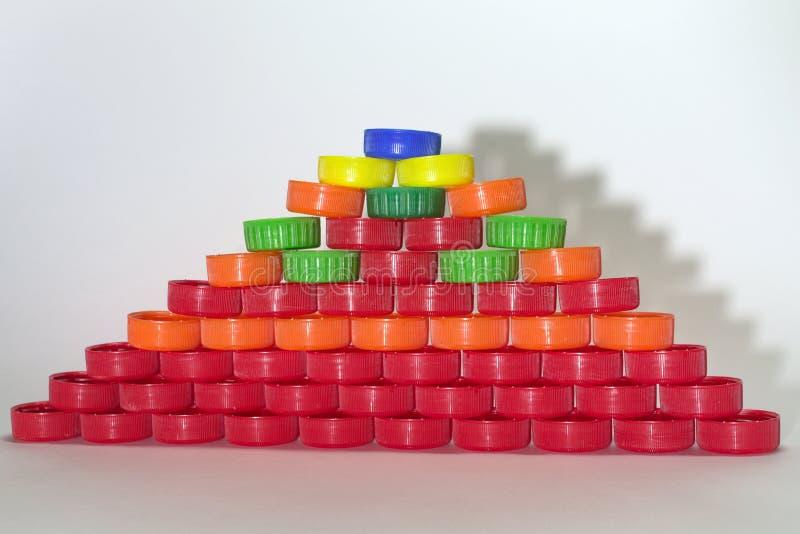 Den plana pyramiden som göras ut ur kulöra plast- kapsyler, gjuter shado arkivfoto