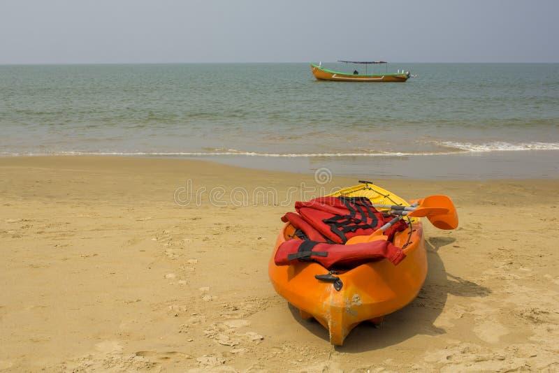 Den plast- guling-apelsinen kajaken med skovlar och röda flytvästar, står på en sandig strand mot bakgrunden av havet och ett sto royaltyfria bilder