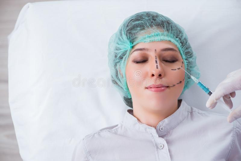 Den plast- kirurgen som förbereder sig för operationen på kvinnaframsida arkivfoton