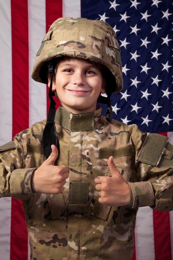 Den pojkeUSA soldaten är visningtum upp framme av amerikanska flaggan. arkivfoto