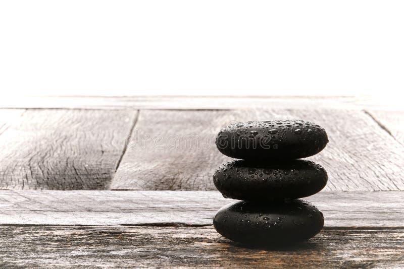 Den polerade våta massagen stenar röset på tappningträ royaltyfria bilder