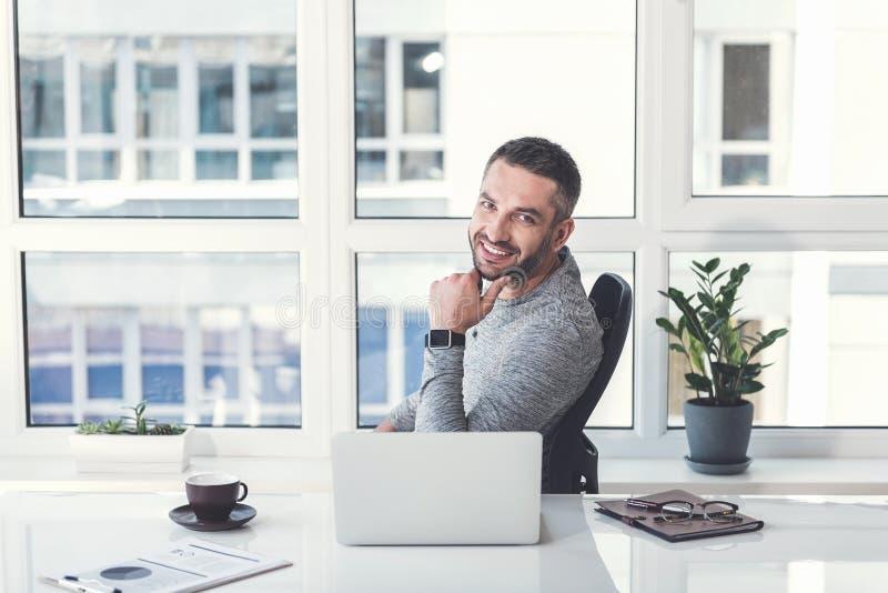Den positiva angenäma mannen tycker om arbete i ljust hemtrevligt kontor royaltyfri foto