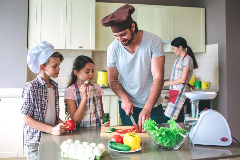 Den positiva farsan klipper tomaten med kniven Flickan rymmer gurkan och äter den Pojken har tomaten i händer och ser vad farsan  arkivbilder