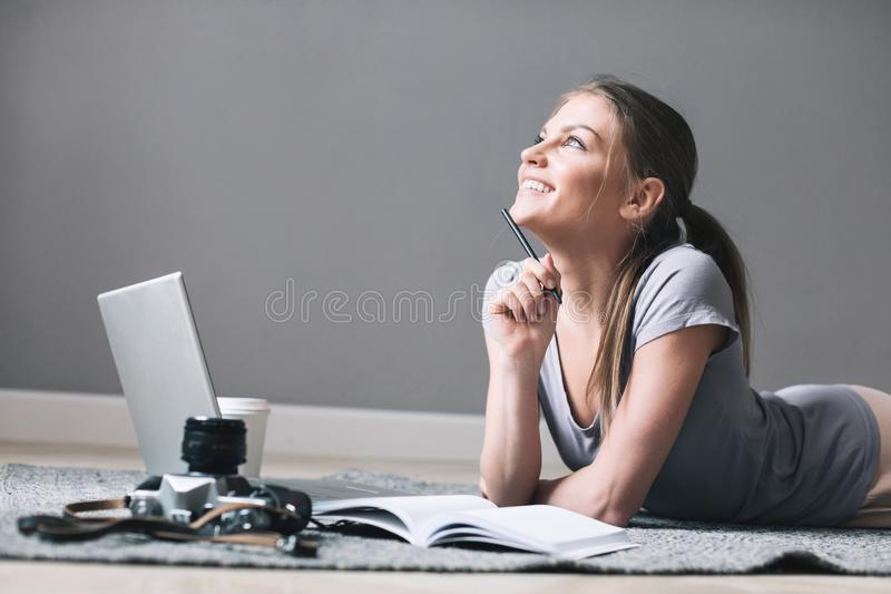Den positiva flickan med bärbara datorn drömmer på golvet arkivfoton