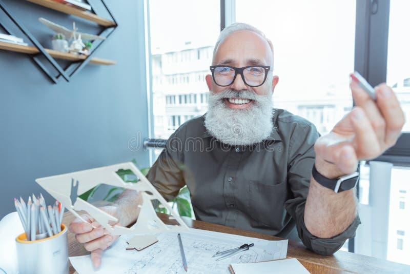 Den positiva gråhåriga arkitekten är den hållande modellen med leende royaltyfri bild