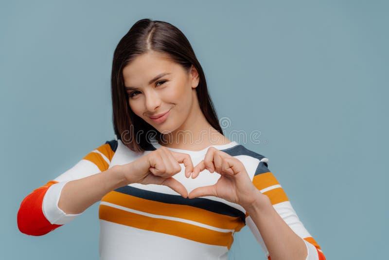 Den positiva kvinnan bekänner förälskat till pojkvännen, gör hjärtagest över bröstkorg, har långt mörkt hår, uttrycker förälskels royaltyfri fotografi