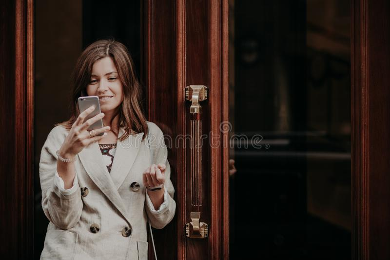 Den positiva lyckliga förtjusta europeiska kvinnan använder bankrörelsen på mobiltelefonen, pratar det online- iklädd vitomslaget fotografering för bildbyråer