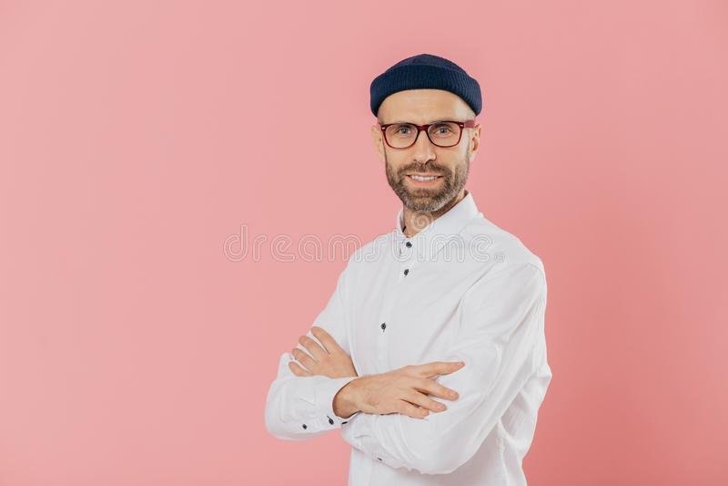 Den positiva manliga entreprenören med självsäkert tillfredsställt ansiktsuttryck, uppehällehänder korsade, ställningar i profil, arkivbilder