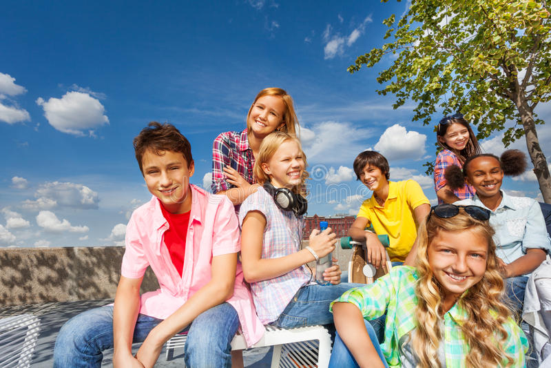 Den positiva multinationella gruppen av ungar sitter tillsammans arkivbild