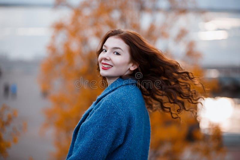 Den positiva och driftiga unga flickan som omkring snärtar hennes hår i luften, medan besöka en höst, parkerar med det gula träde fotografering för bildbyråer