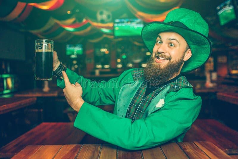 Den positiva och gladlynta unga mannen i grön dräkt sitter på tabellen i bar Han pekar rånar på med mörkt öl Grabben ser lycklig royaltyfri fotografi