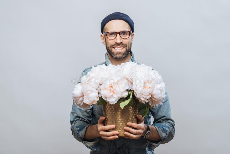 Den positiva orakade mannen bär anblickar, rymmer den härliga buketten av blommor som går att framlägga dem till hans fru och att royaltyfri bild