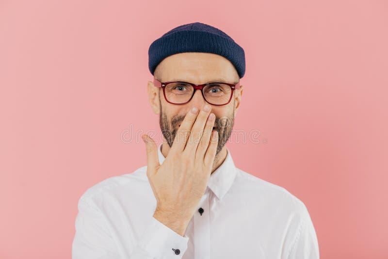 Den positiva orakade mannen täcker munnen med gömma i handflatan, fniss positivt, bär anblickar, hör det roliga skämtet, modeller fotografering för bildbyråer
