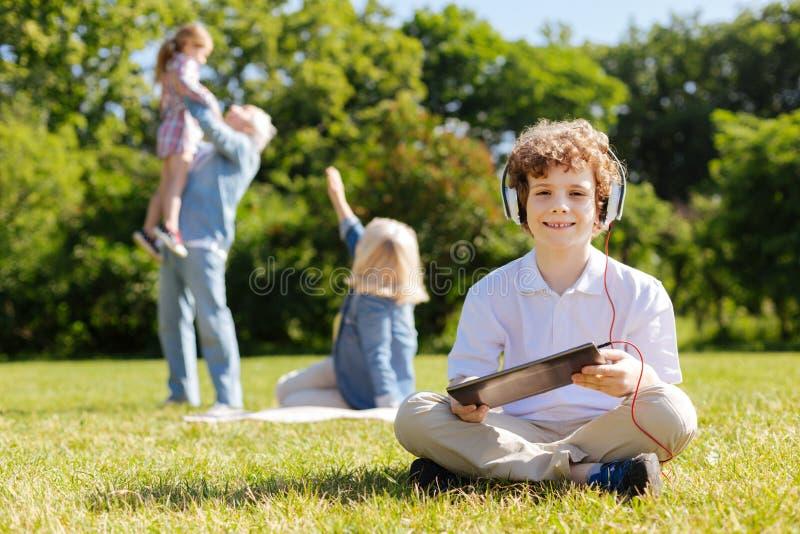 Den positiva pojkekorsningen lägger benen på ryggen, medan sitta på gräset royaltyfri fotografi