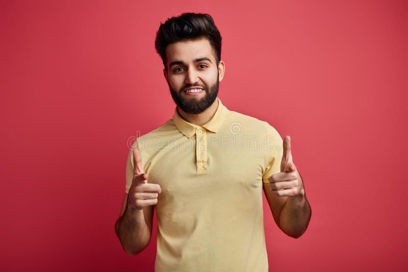 Den positiva skäggiga mannen i tillfällig kläder indikerar lyckligt på kameran royaltyfria foton
