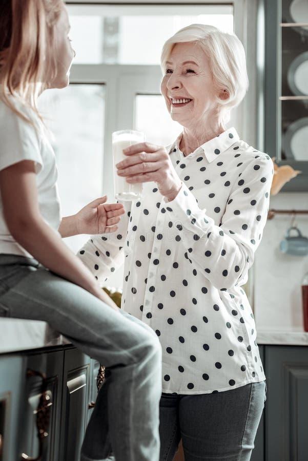 Den positiva stilfulla farmodern som ler till flickan, medan ge hennes något, mjölkar royaltyfria foton