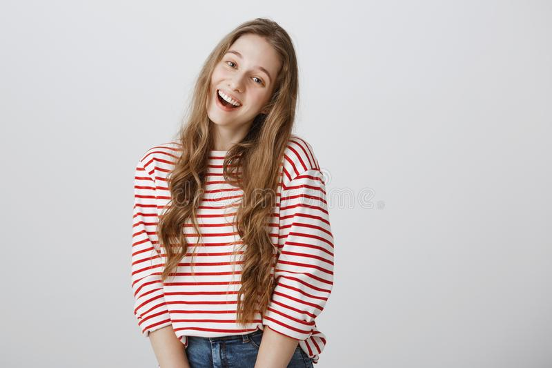 Den positiva tonåringen hälsar hennes bästa vän Det inomhus skottet av det enfaldiga snygga anseendet för den unga kvinnan i gull arkivfoton