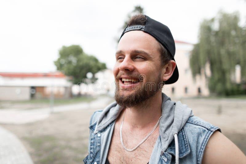 Den positiva unga hipstermannen i trendig jeans tilldelar ett stilfullt lock med ett skägg på gatan på en varm sommardag arkivbilder