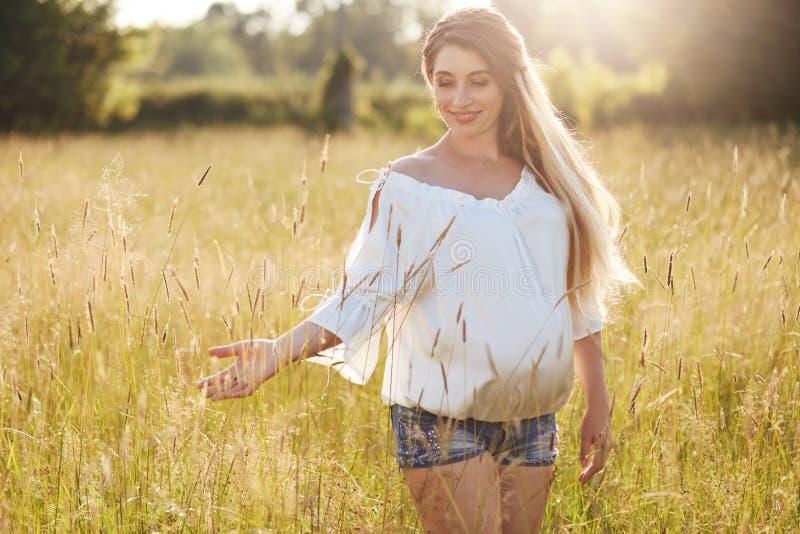 Den positiva unga kvinnlign förutser för behandla som ett barn, promenader över vetefält, tycker om den soliga dagen, grönt gräs  arkivbilder