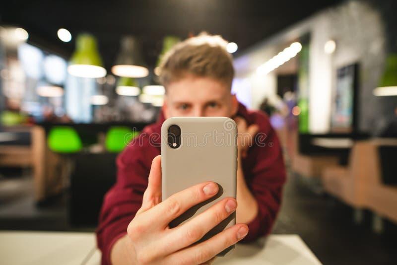 Den positiva unga mannen tar ett foto på en smartphone i en snabbmatsrestaurang, en smartphone royaltyfri foto