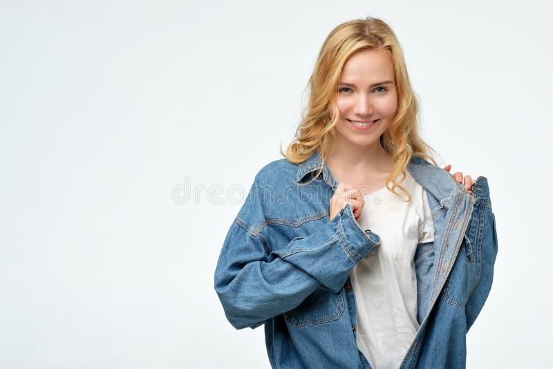 Den positiva uppnosiga caucasian blonda flickan i jeans klår upp att le på kameran royaltyfri bild