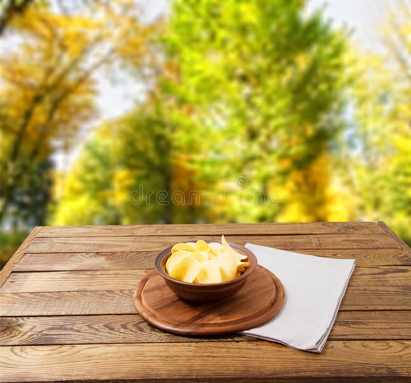 Den potatischiper och servetten, på trätabellen på gjort suddig parkerar bakgrund Borddukferiebegrepp royaltyfri fotografi