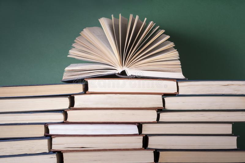 Den ?ppna boken, inbunden bok bokar p? tr?tabellen sax och blyertspennor p? bakgrunden av kraft papper tillbaka skola till Kopier royaltyfri fotografi