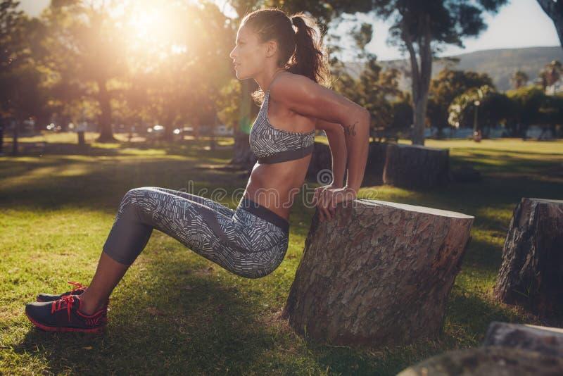 Den praktiserande muskulösa kvinnan skjuter ups i en parkera arkivfoto