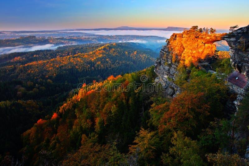 Den Pravcicka branaen vaggar bromonumentet i höstfärger Den tjeckiska nationalparken Ceske Svycarsko, bohemmet Schweiz parkerar,  arkivfoto