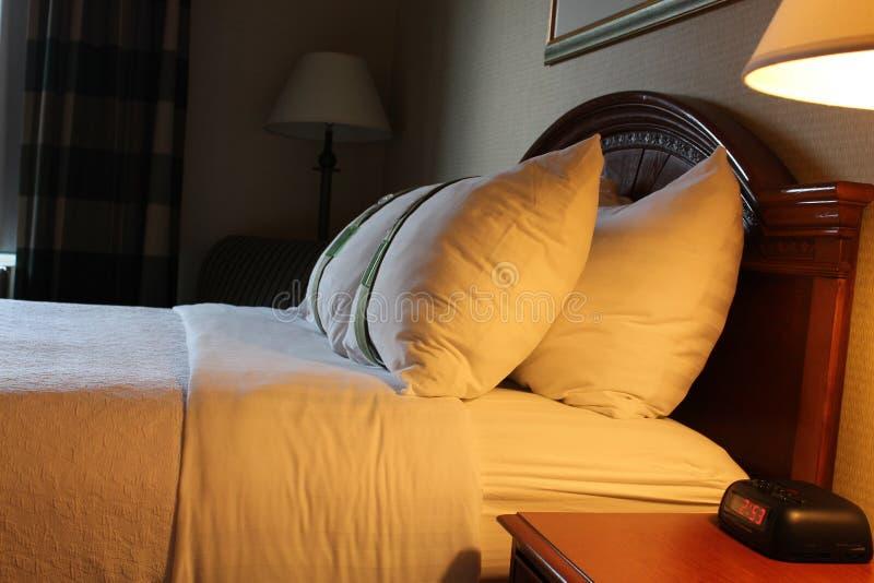 Den precis gjort sängen och fluffigt kudder i hotell arkivbilder