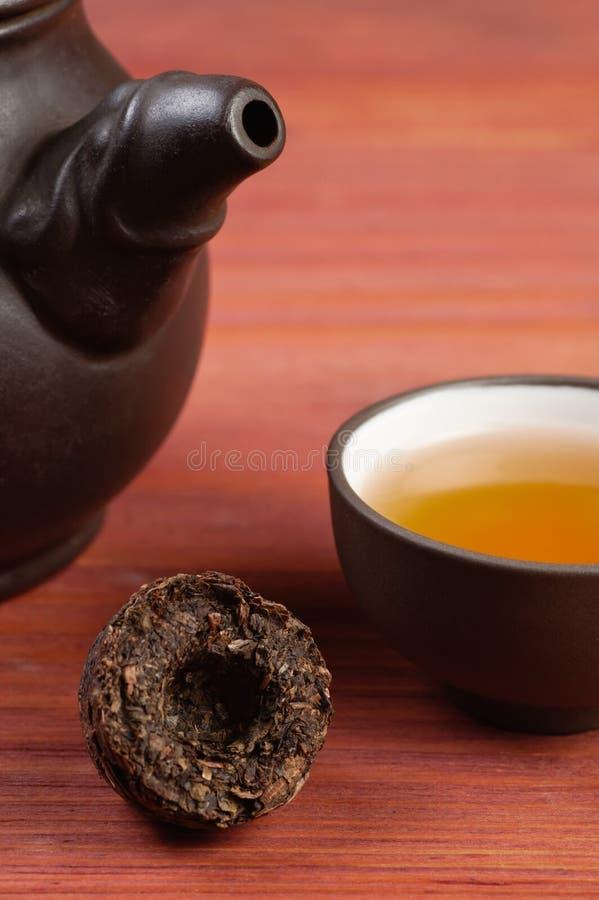 Den pressande briketten för pu-erhteblad med lera glasade teabowl och delen av leratekannan på den röda trätabellen arkivfoton