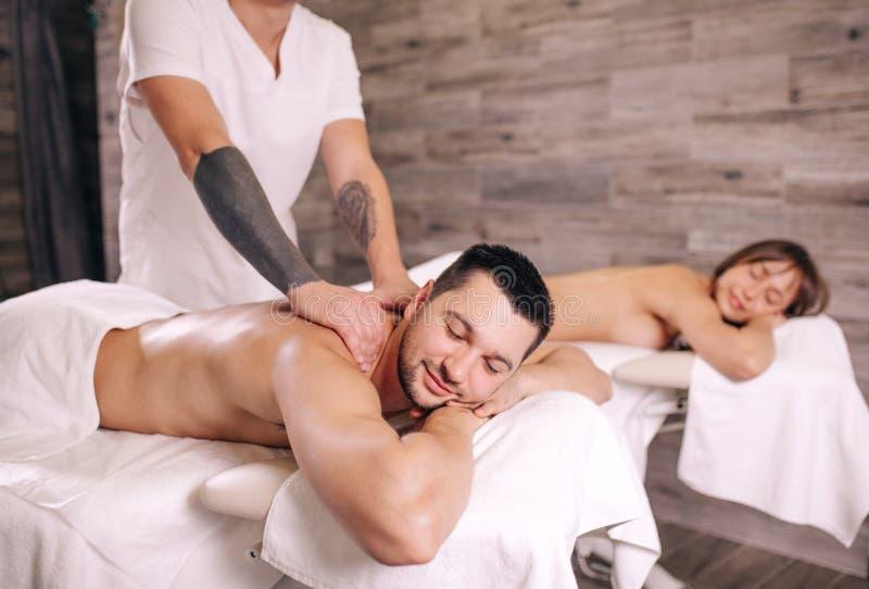 Den prydde med pärlor stiliga mannen är lycklig att få massage från yrkesmässig massör royaltyfria bilder