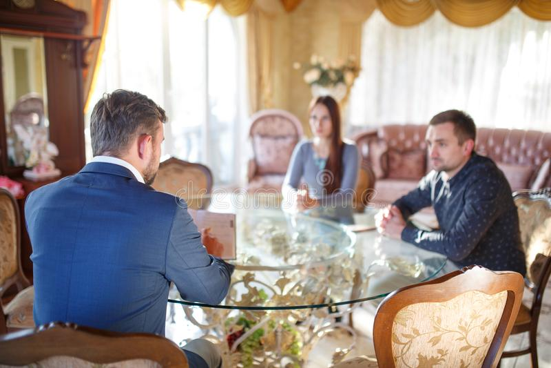 An den Psychologe Youngs-Paaren, die an einem Glastisch hört auf einen Doktor sitzen lizenzfreies stockbild