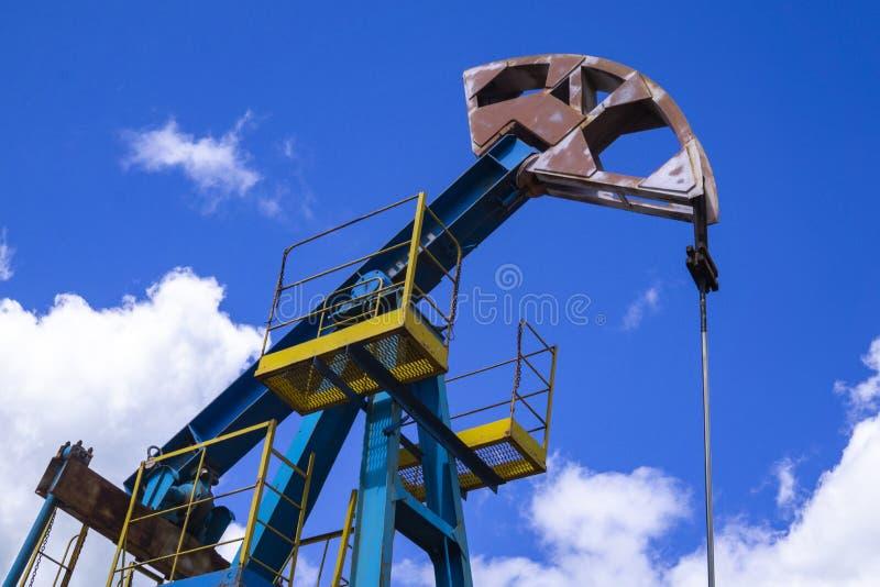 Den pumpa enheten för strålen är läxa, solnedgång i oljefält F?r oljeplattformenergi f?r olje- pump industriell maskin f?r oljor  royaltyfria foton