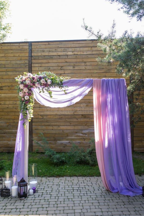 Den purpurfärgade bröllopbågen dekorerade med blommor, lilan och rosa färgmaterial Den härliga plattformen för en bröllopceremoni fotografering för bildbyråer