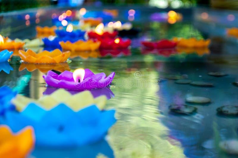 Den purpurfärgade lotusblommaformstearinljuset tände och flötet på vatten royaltyfri bild