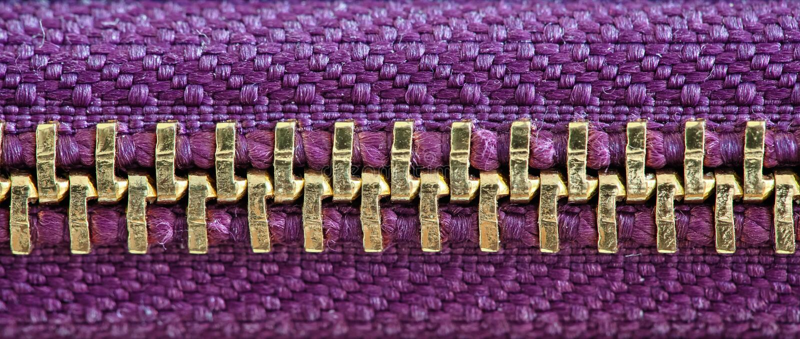 Den purpurfärgade och guld- blixtlåset stängde stramt bandet tillsammans två lager av tygtextilen under den höga förstoringsslutd royaltyfri bild