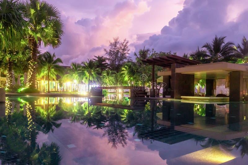 Den purpurfärgade reflexionen av himlen i vattnet i aftonen Palmträd, gröna växter och en härlig solnedgång hotell i Khao Lak, arkivbild