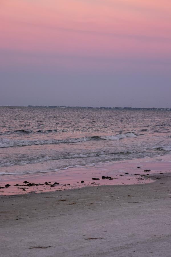 Den purpurfärgade solnedgången reflekterar på vatten och sand av fortet Myers Beach, royaltyfria bilder