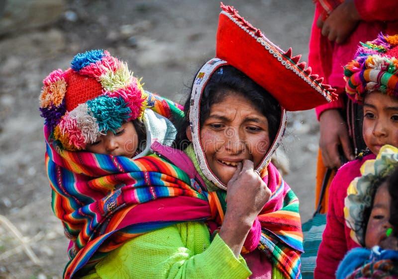 Den Quechua modern och behandla som ett barn i en by i Anderna, Ollantaytambo royaltyfria foton