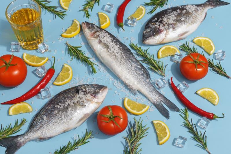 Den rå doradafisken med kryddor, saltar, citronen och örter, rosmarin på enblått bakgrund Top beskådar royaltyfri bild