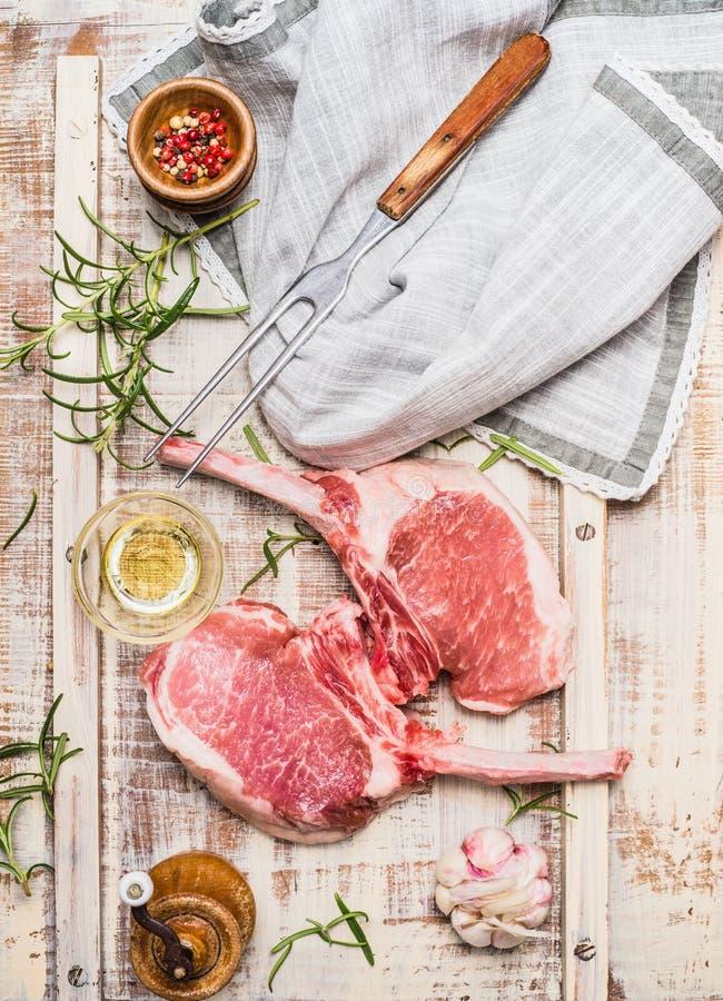 Den rå gourmet- grisköttkotletten för galler, BBQ eller matlagning med örter, kryddor och kött dela sig på ljus lantlig bakgrund, arkivbild