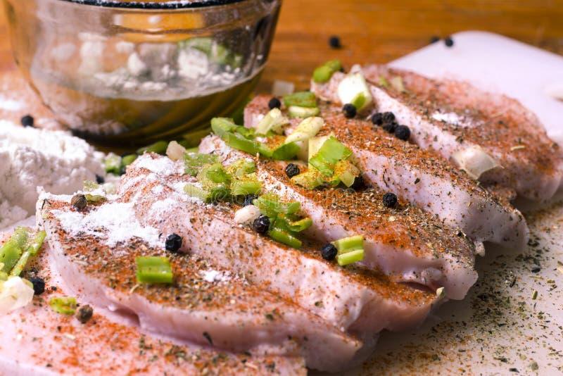 Den rå grisköttfransyskan hugger av på en skärbräda med örter, rosmarin, timjan, chili som är salt, peppar på den vita skärbrädan royaltyfria bilder