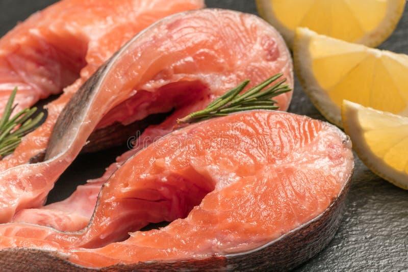 Den rå laxen, forellbiff på ett mörker kritiserar bakgrund Lös atlantisk fisk sund mat arkivfoton
