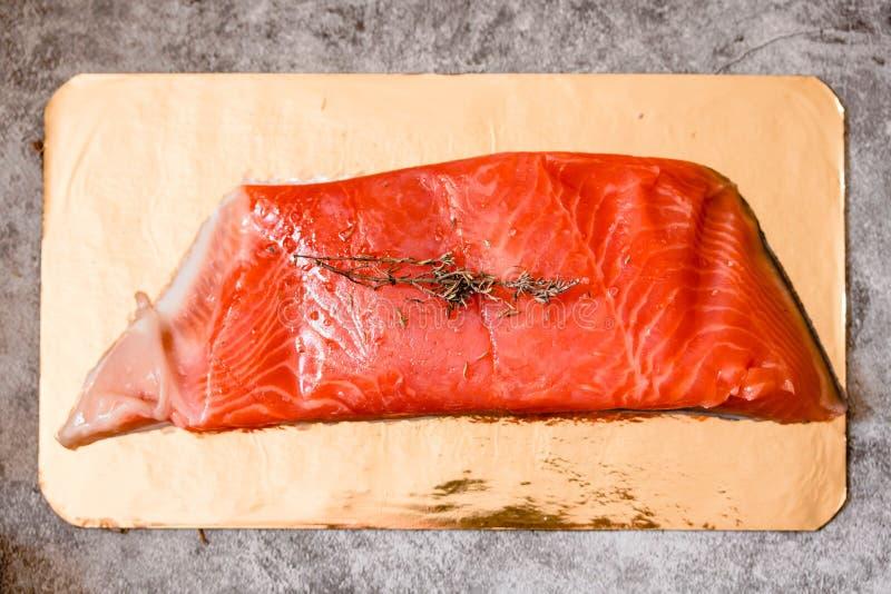 Den rå laxfileten på guld- bräde och grå färger kritiserar bakgrund, lös atlantisk fisk Sunt matlagningbegrepp royaltyfri bild