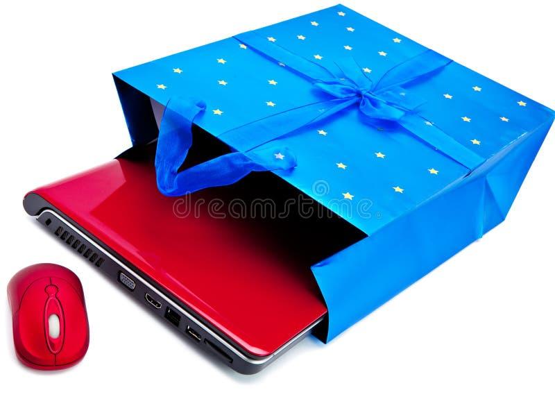 Den röda bärbara datorn och en datormus packas in i ett gåvapaket arkivfoton